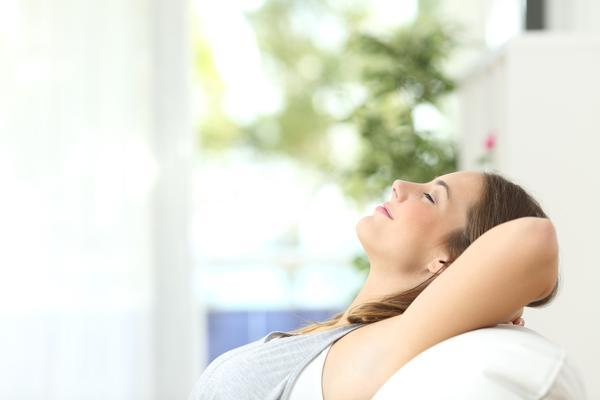 Profile of a beautiful woman relaxing lying on a couch at home